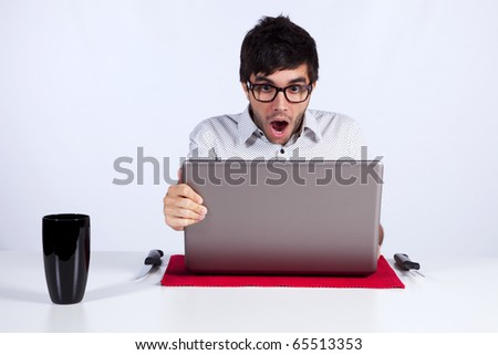 young man shocked with something he see on his laptop computer - stock photo