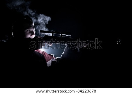 young man shooting with a rifle (color toned image) - stock photo