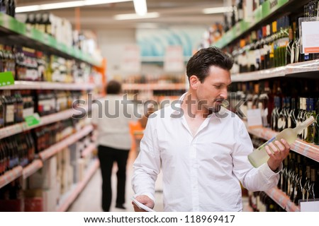 Young man shopping for liquor at supermarket - stock photo