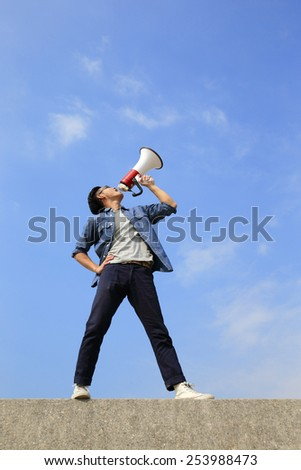 young man shout by megaphone with blue sky background, asian - stock photo