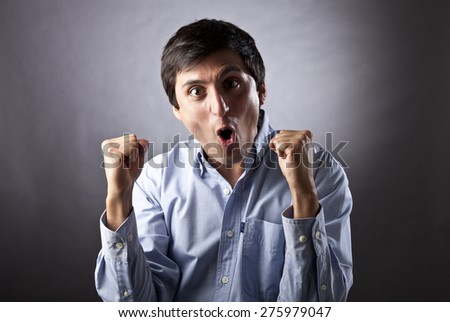 Young Man Shouting and feasting I fill of happiness and emotion on gray background - stock photo