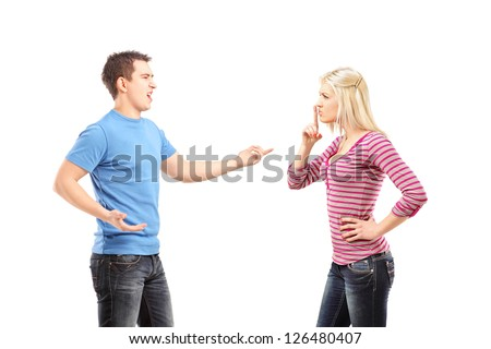 Young man shouting and woman gesturing silence isolated on white background - stock photo