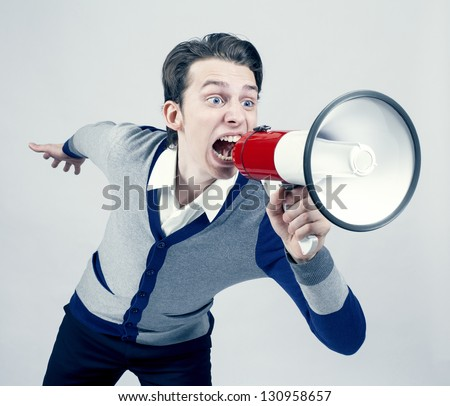 young man shouting into a megaphon - stock photo