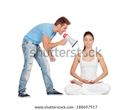 Young man shouting through a megaphone at a woman focused while doing yoga - stock photo