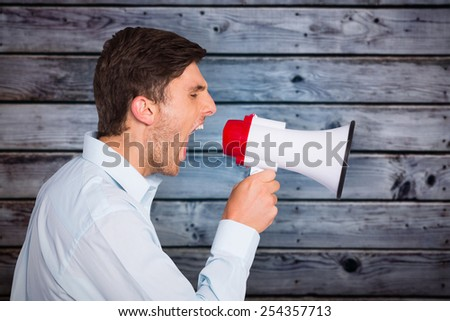 Young man shouting through megaphone against grey wooden planks - stock photo