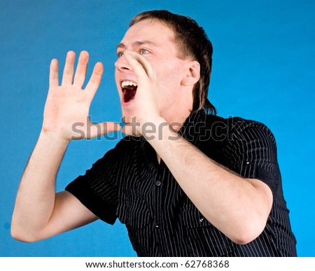 Young man shouting with hands cupped to his mouth on blue background - stock photo