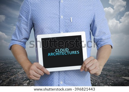 young man showing digital tablet with CLOUD ARCHITECTURES in city , business concept ,business idea , analysis concept - stock photo