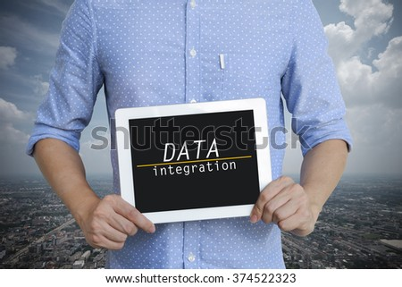 young man showing digital tablet with DATA INTEGRATION on sky background  , business concept ,business idea - stock photo