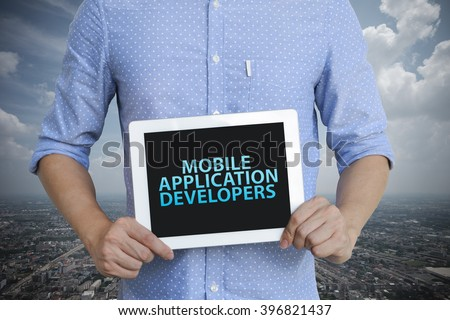 young man showing digital tablet with MOBILE APPLICATION DEVELOPERS  in city , business concept ,business idea , analysis concept - stock photo