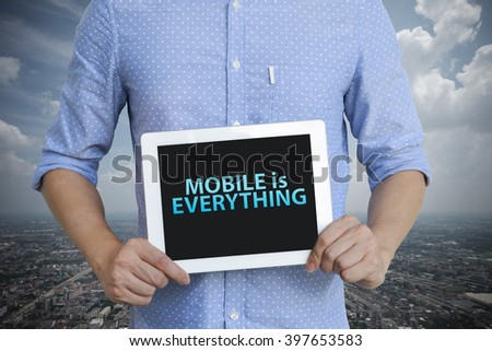 young man showing digital tablet with  MOBILE IS EVERYTHING  in city , business concept ,business idea , analysis concept - stock photo