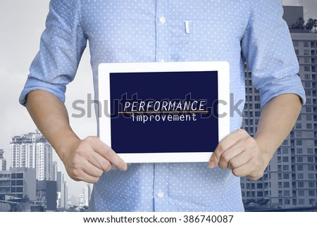 young man showing digital tablet with PERFORMANCE IMPROVEMENT in city  , business concept ,business idea , strategy concept - stock photo