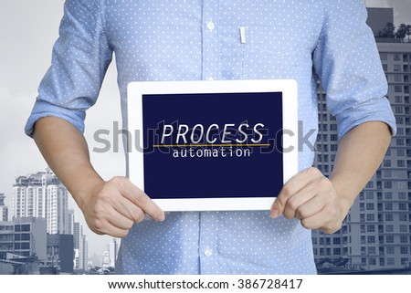 young man showing digital tablet with PROCESS AUTOMATION in city  , business concept ,business idea , strategy concept - stock photo