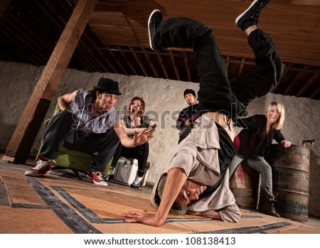 Young man showing friends freestyle moves on cardboard - stock photo