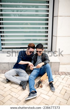 Young man showing his friend some video or photo on the smartphone - stock photo