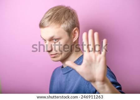 Young man showing stop stop. Gesture. On a purple background. - stock photo