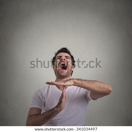 Young man showing time out hand gesture, frustrated screaming to stop isolated on gray wall background. Too many things to do. Human emotions face expression reaction - stock photo