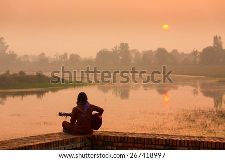 Young man singer singing on his guitar on the lake at a beautiful sunset - stock photo