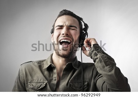 Young man singing while listening to music - stock photo
