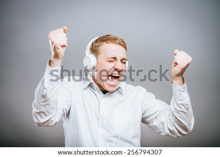 young man singing with loud music in the ears - stock photo