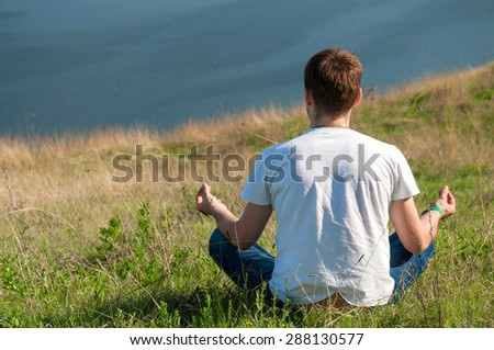 Young man sits on the top of the hill viewing wide Dnister river. Yoga meditation - stock photo