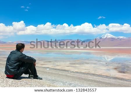 Young man sitting alone on the shore of Laguna Colorada, Bolivia - stock photo