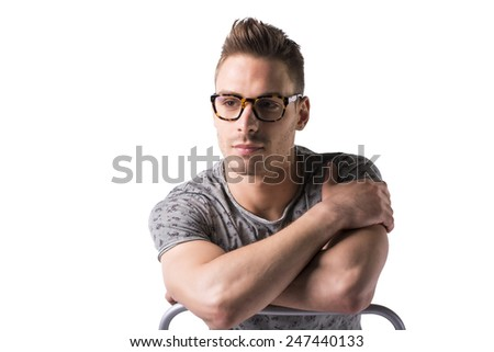 Young man sitting and leaning against chair's back, with glasses. Isolated on white - stock photo