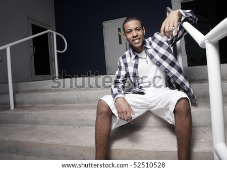 Young man sitting and smiling - stock photo