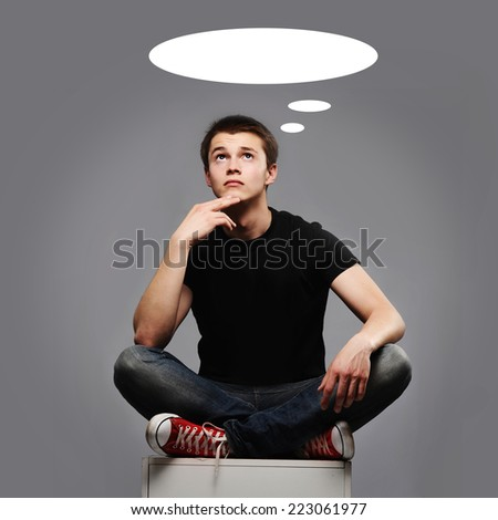 young man sitting and thinking about something - stock photo