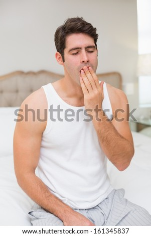 Young man sitting and yawning in bed at home - stock photo