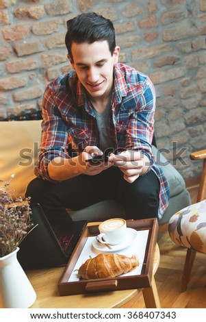 Young man sitting at a cafe, taking a snapshot of his food  - stock photo