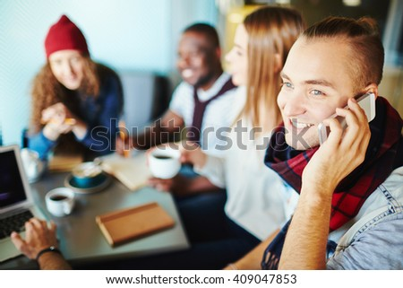Young man sitting at cafe with friends and talking on the phone - stock photo