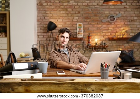 Young man sitting at desk, working with laptop computer, looking at camera. - stock photo