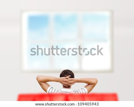 Young man sitting at his new home and looking at window. Photo from behind - stock photo