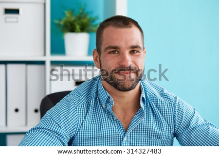 Young man sitting behind a desk in modern office - stock photo