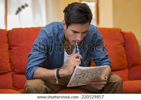 Young man sitting doing a crossword puzzle looking thoughtfully at a magazine with his pencil to his mouth as he tries to think of the answer to the clue - stock photo