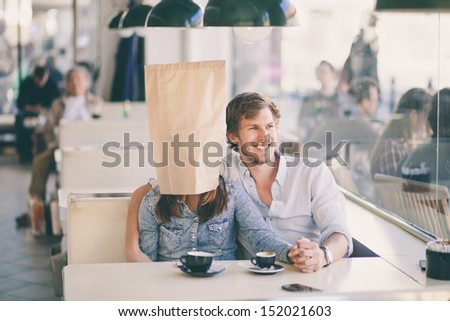 Young man sitting in a cafe with his girlfriend who's wearing a paper bag over her head - stock photo