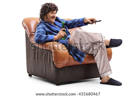 Young man sitting in an armchair with a beer in his hand and changing channels on TV isolated on white background - stock photo