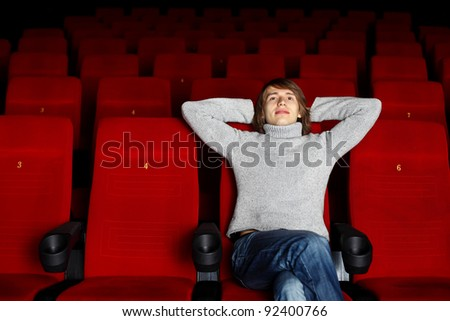Young man sitting in cinema and watching movie - stock photo