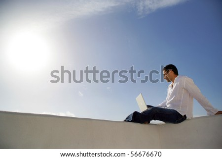 Young man sitting in front of a laptop computer face to the sea - stock photo