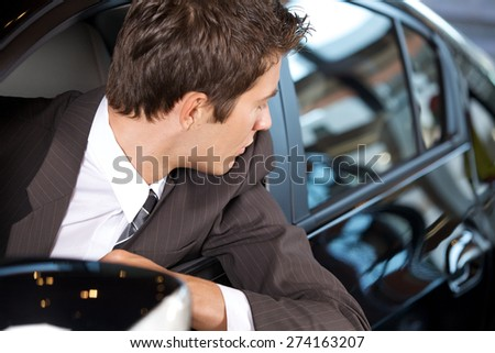 Young man sitting in new car - stock photo