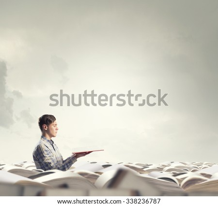 Young man sitting in pile of old books - stock photo