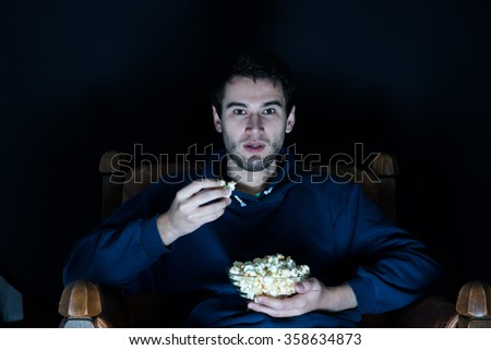 young man sitting in the dark room in the front of tv watching movie and eating popcorn - stock photo
