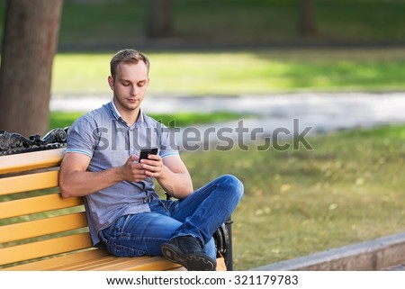 Young man sitting in the park and using a smart phone  - stock photo