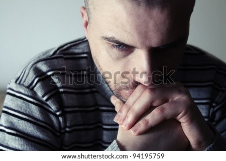 Young man sitting looking upset - stock photo