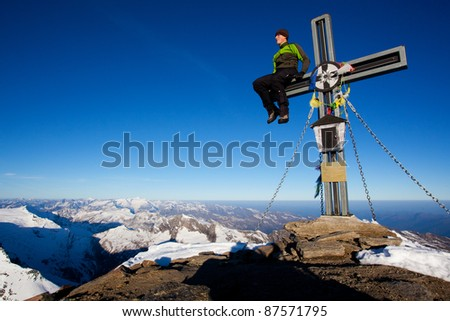 Young man sitting on a summit cross in the Alps - stock photo