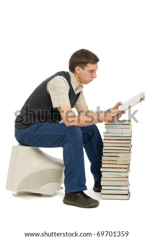 Young man sitting on an old monitor and reads a book. Book instead of a computer. - stock photo