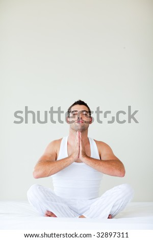 Young man sitting on bed doing yoga with copy-space - stock photo