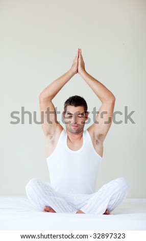 Young man sitting on bed in meditation pose - stock photo