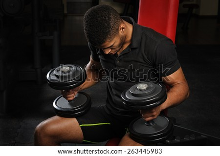young man sitting on bench at gym - stock photo