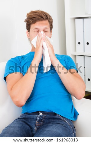 Young Man Sitting On Couch Blowing His Nose - stock photo